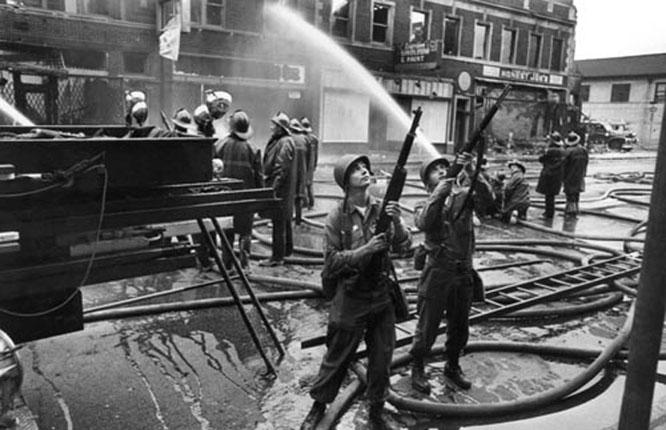 Kravallerna 1967 var början på slutet, enligt den svarte borgmästaren Coleman Young. Tusentals butiker plundrades och över 2000 byggnader förstördes.Soldater fick kallas in för att förstärka polisen och som här skydda brandkåren när den skulle släcka bränderna.