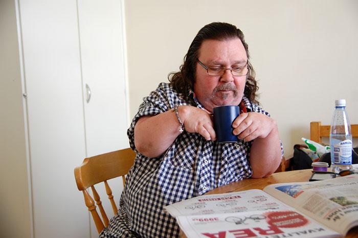 stig har endast tre procents muskelstryrka kvar i sina händer, men eftersom han kan lyfta sin kaffekopp själv, visserligen endast med bägge händer, ansåg Försäkringskassan att han inte behövde fortsatt assistans.   Foto: Nya Tider
