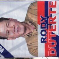"""Rodrigo """"Rody"""" Duterte, 71, på en av otaliga valaffischer för de olika kandidaterna. Valaffischer återfinns på snart när varje hus och tricykeltaxi, då fattiga människor ser valtider som en inkomstmöjlighet. Detta då kandidater till lokala befattningar i provinserna, som till exempel borgmästare, köper röster i stor omfattning. Röstköpen skedde tidigare diskret på nätterna, men i årets val har de skett öppet på dagtid. I kandidatens eller partiets informationsmaterial läggs en sedel motsvarande tio kronor eller mer och delas ut till enskilda personer. Familjeöverhuvuden till större familjer kan få närmare motsvarande 1 000 kronor och hela Barangay (kommundistrikt) eller byar kan köpas för cirka 10 000 kr. Fattigdomsnivån avgör priset. Det är inte ovanligt att människor tar emot betalning från flera kandidater."""