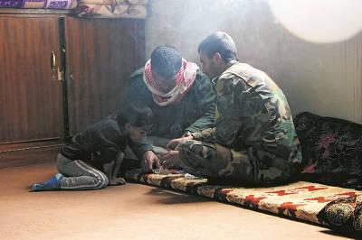Jezidisoldater tar en rökpaus. Dessa jezidimän kämpar mot Islamiska staten i Sinjars berg. De var mycket gästvänliga och hade slaktat ett lamm dagen till ära.