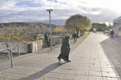 med blicken i marken vandrar kvinnan mot Hjällbo centrum. I centrum ser man sällan utländska kvinnor utan en slöja på, och svenska unga kvinnor blir titt som tätt tillsagda att de borde täcka sitt hår. Foto: Nya Tider